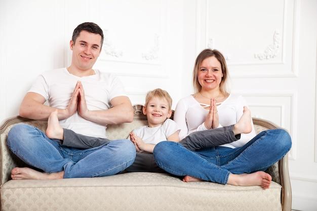 Retrato de uma família fofa com filho posando em pose de ioga no sofá