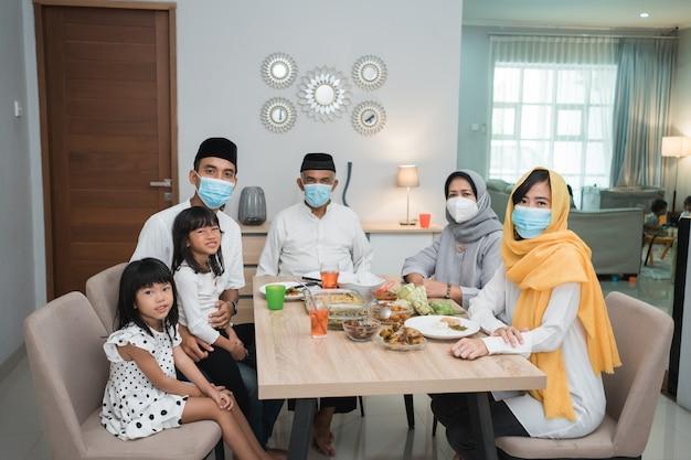 Retrato de uma família muçulmana feliz usando máscara durante a celebração do eid mubarak em casa