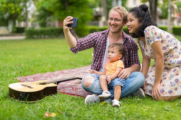 Retrato de uma família multiétnica feliz com uma criança se unindo ao ar livre