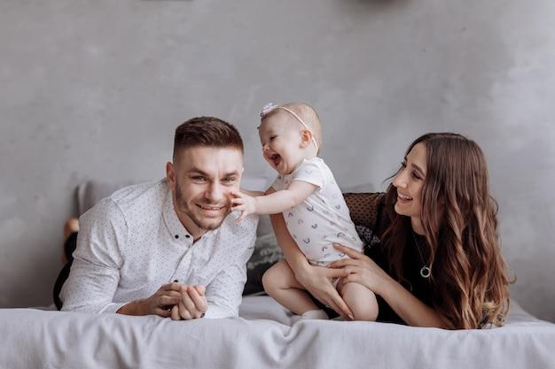 Retrato de uma família na cama em casa enquanto brincava com seu bebê - pai, mãe e filha de um ano se divertem juntos - momento de intimidade - copie o espaço.