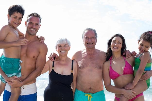 Retrato de uma família sorridente de várias gerações na praia