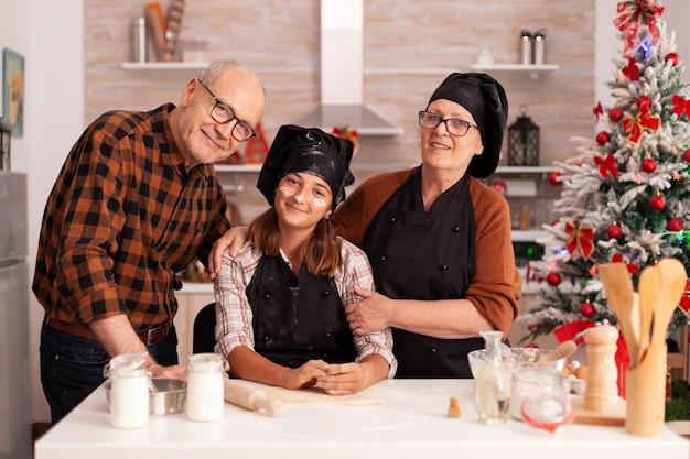 Retrato de uma família sorridente em pé à mesa em uma cozinha culinária decorada de natal
