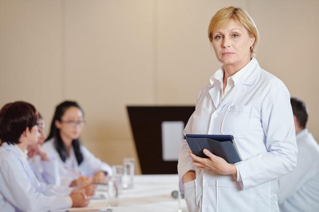 Retrato de uma farmacologista feminina séria com um computador tablet em pé diante de uma mesa grande na sala de reuniões