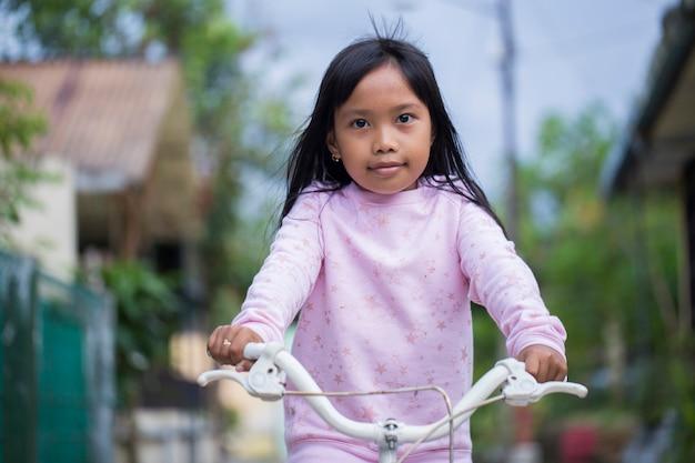 Retrato de uma feliz alegre criança asiática andando de bicicleta