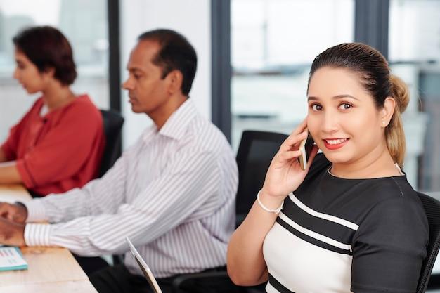 Retrato de uma feliz empresária indiana falando ao telefone com um parceiro de negócios, sentado na mesa do escritório ao lado de colegas