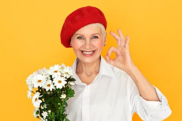 Retrato de uma florista atraente, alegre, de meia-idade, com chapéu vermelho, tendo uma expressão facial confiante, fazendo um gesto certo, segurando um monte de margaridas, organizando flores para um evento especial