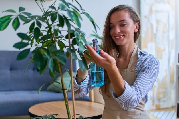 Retrato de uma fofa feliz jovem atraente com avental regando plantas domésticas usando um spray