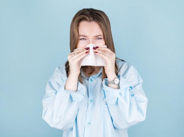 Retrato de uma fofa mulher caucasiana insalubre com um guardanapo de papel, espirra, apresenta sintomas de alergia, resfriou-se. mulher desesperada e doente tem gripe.