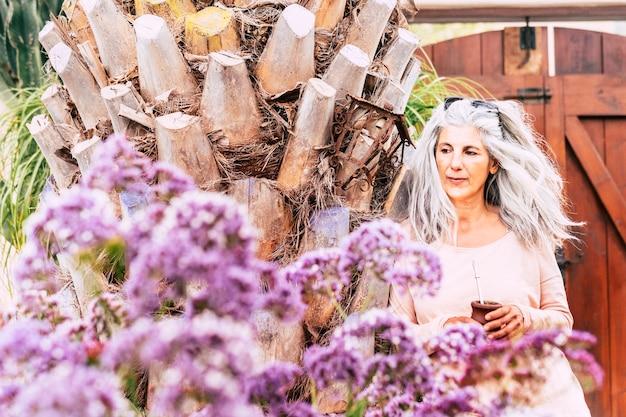 Retrato de uma fofa mulher caucasiana madura com longos cabelos brancos na moda bebendo um chá naturel em um jardim fora de casa