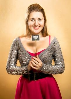 Retrato de uma fofa mulher sorridente posando com placa decorativa de coração