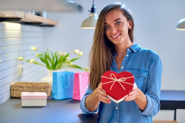 Retrato de uma fofa satisfeita alegre feliz sorrindo feliz mulher amada com caixa de presente em forma de coração para um dia de feriado