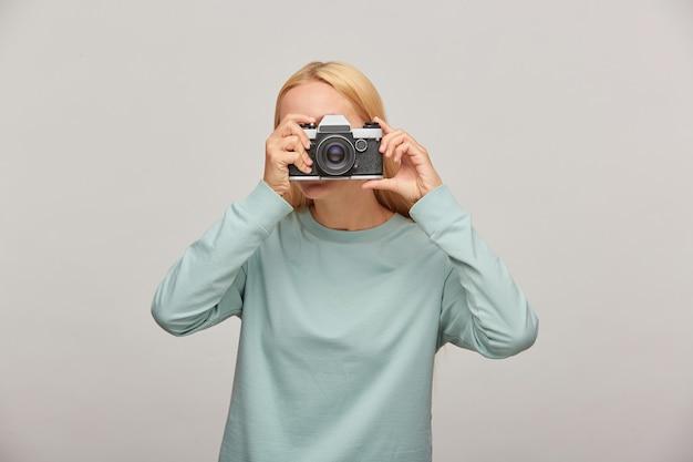 Retrato de uma fotógrafa cobrindo o rosto com a câmera