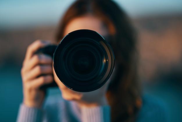 Retrato de uma fotógrafa com uma câmera profissional ao ar livre nas montanhas.