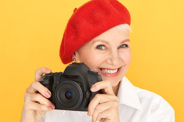 Retrato de uma fotógrafa madura e enérgica, com cabelo curto e rugas, tirando fotos usando uma câmera profissional preta