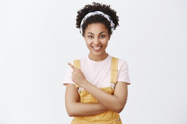 Retrato de uma funcionária morena encantadora e otimista, de macacão amarelo e faixa na cabeça, apontando para o canto superior esquerdo enquanto sorri com expressão segura e gentil sobre a parede cinza