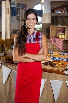 Retrato de uma funcionária sorridente em pé com os braços cruzados na padaria
