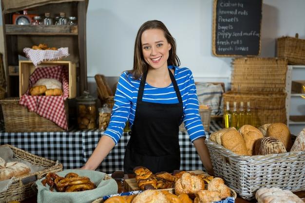 Retrato de uma funcionária sorridente em pé no balcão de pão
