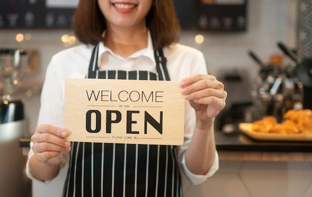 Retrato de uma garçonete asiática feliz em pé em uma cafeteria segurando uma placa aberta enquanto reabrindo o atendimento durante a pandemia de coronavírus, proprietário de uma pequena empresa e iniciante com um conceito de cafeteria