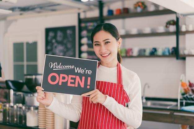 Retrato de uma garçonete em pé no portão de sua cafeteria com uma tabuleta aberta