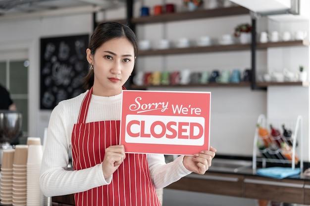 Retrato de uma garçonete em pé no portão de sua cafeteria com uma tabuleta fechada
