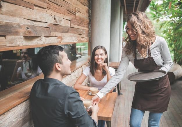 Retrato de uma garçonete servindo café para um cliente de casal