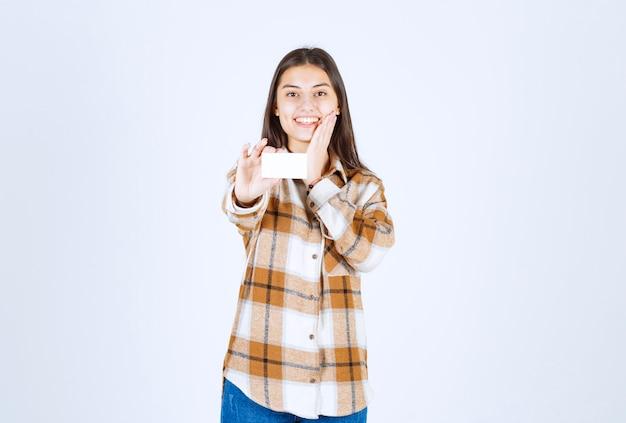 Retrato de uma garota adorável, mostrando o cartão de visita na parede branca.