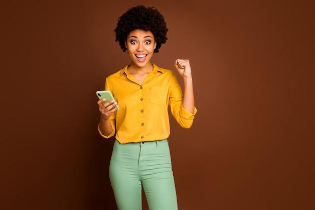 Retrato de uma garota afortunada afro americana estudante blogueira usar smartphone celebrar loteria online levantar punhos gritar sim usar calças verdes amarelas calças isoladas cor marrom