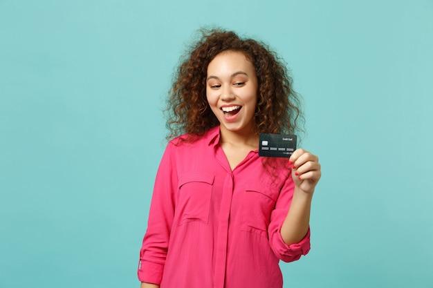 Retrato de uma garota africana animada em roupas rosa casuais, segurando o cartão do banco de crédito isolado no fundo da parede azul turquesa no estúdio. emoções sinceras de pessoas, conceito de estilo de vida. simule o espaço da cópia.
