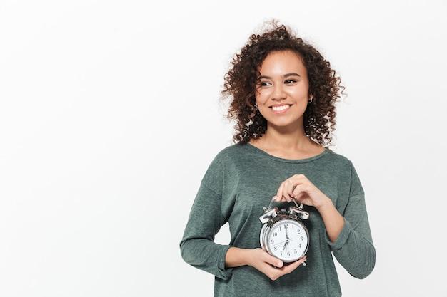 Retrato de uma garota africana casual muito alegre em pé isolado sobre uma parede branca, mostrando o despertador
