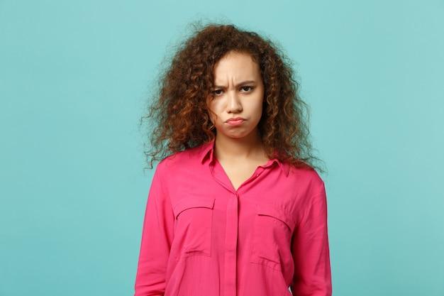 Retrato de uma garota africana ofendida em roupas casuais, olhando a câmera, soprando as bochechas isoladas no fundo da parede azul turquesa no estúdio. emoções sinceras de pessoas, conceito de estilo de vida. simule o espaço da cópia.