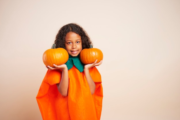 Retrato de uma garota africana segurando duas abóboras de halloween
