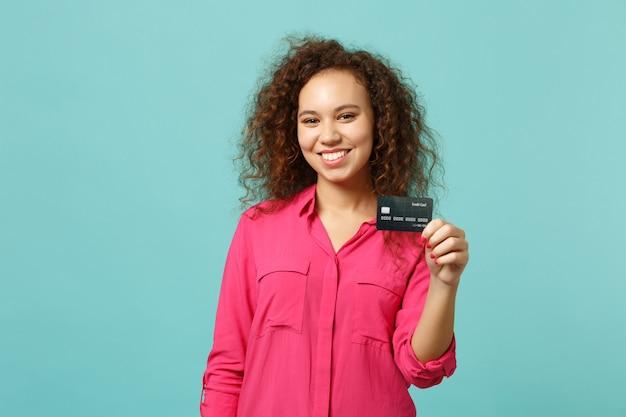 Retrato de uma garota africana sorridente em roupas rosa casuais, segurando o cartão do banco de crédito isolado no fundo da parede azul turquesa no estúdio. emoções sinceras de pessoas, conceito de estilo de vida. simule o espaço da cópia.