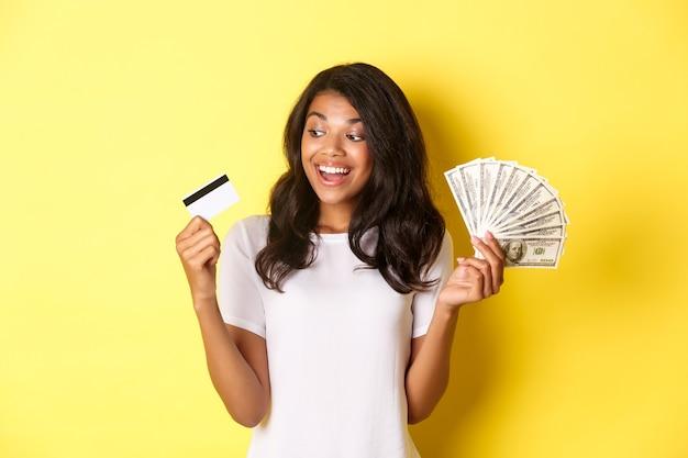Retrato de uma garota afro-americana atraente segurando dinheiro e olhando para o cartão de crédito