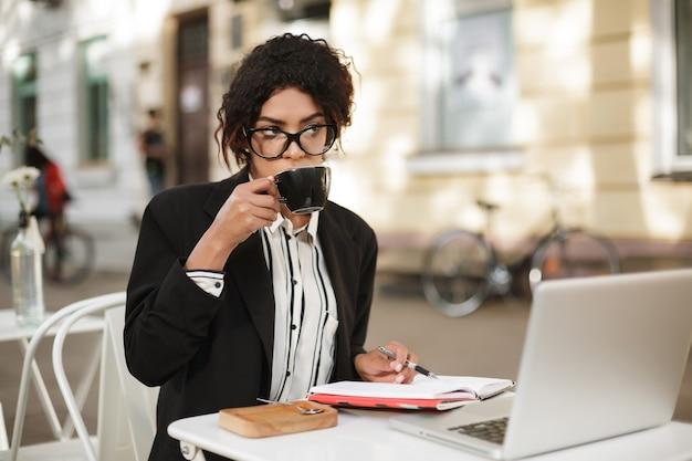 Retrato de uma garota afro-americana de óculos, sentada à mesa do café com laptop e notebook na mesa