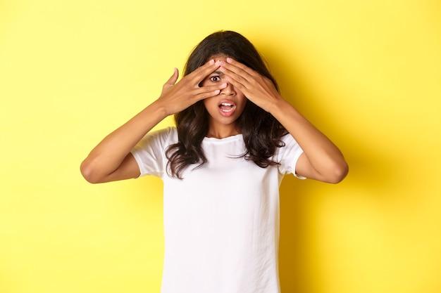 Retrato de uma garota afro-americana envergonhada e chocada fechando os olhos, mas espiando por entre os dedos