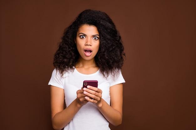 Retrato de uma garota afro-americana espantada e chocada, usar o telefone celular, ler as informações da rede social, maravilha, gritar, uau, usar roupas elegantes.