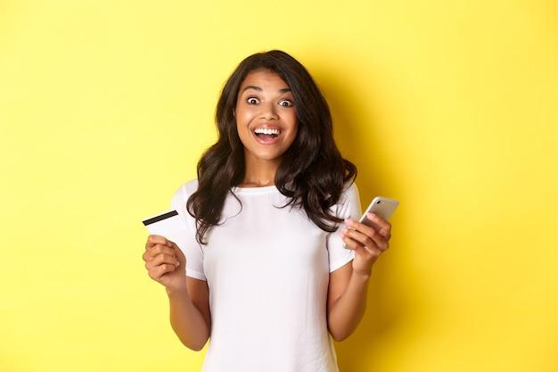 Retrato de uma garota afro-americana espantada, segurando o smartphone e o cartão de crédito em pé sobre as costas amarelas.