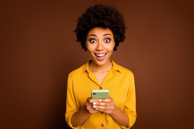 Retrato de uma garota afro-americana espantada usando smartphone ler notícias maravilhosas de mídia social impressionado gritar uau omg usar roupas amarelas bonitas isoladas sobre a cor marrom