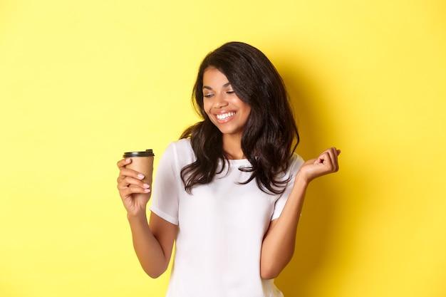 Retrato de uma garota afro-americana feliz e satisfeita, olhando para o café e sorrindo, em pé sobre um fundo amarelo