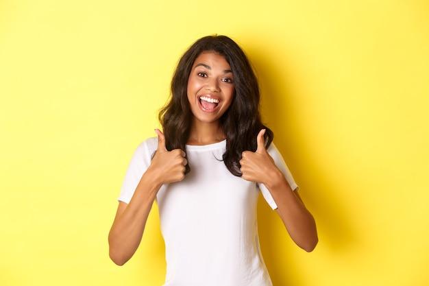 Retrato de uma garota afro-americana fofa e alegre mostrando o polegar para cima em apoio, curtindo e concordando com você, elogiando o excelente trabalho