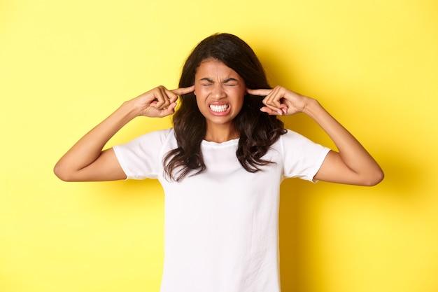 Retrato de uma garota afro-americana irritada e irritada fechando os ouvidos e fazendo uma careta de um som horrível