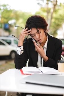 Retrato de uma garota afro-americana sentada à mesa com óculos na mão e fechando os olhos cansada enquanto fala no celular
