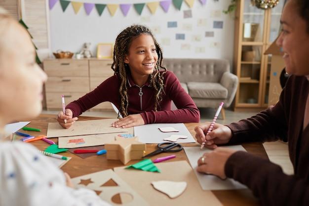 Retrato de uma garota afro-americana sorridente, olhando para a professora enquanto desfruta da aula de arte e artesanato na escola, copie o espaço