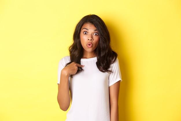 Retrato de uma garota afro-americana surpresa, apontando o dedo para si mesma em pé sobre um fundo amarelo