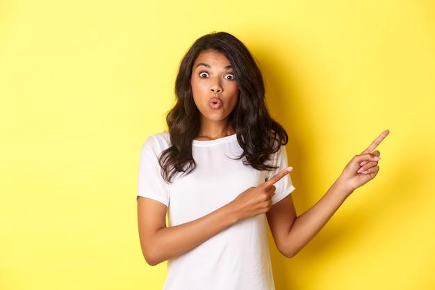 Retrato de uma garota afro-americana surpresa e impressionada dizendo uau parecendo espantada ao apontar