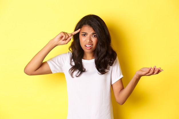 Retrato de uma garota afro-americana zangada e confusa repreendendo alguém por ser estúpido apontando