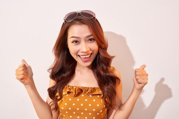 Retrato de uma garota alegre da moda enlouquecendo em um vestido de bolinhas laranja isolado em bege