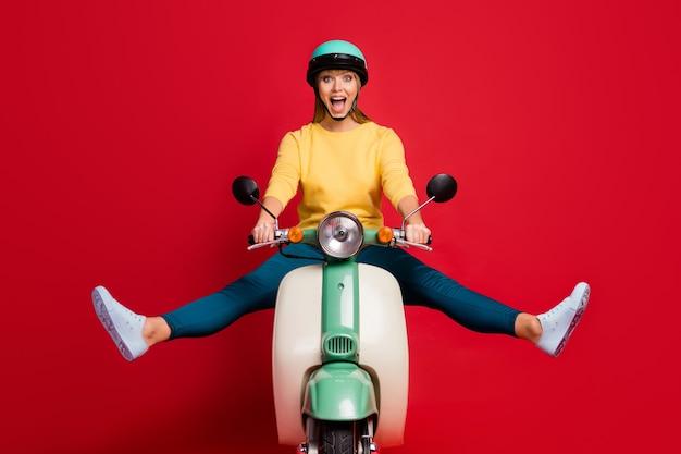 Retrato de uma garota alegre e feliz dirigindo uma motoneta gritando com a boca aberta