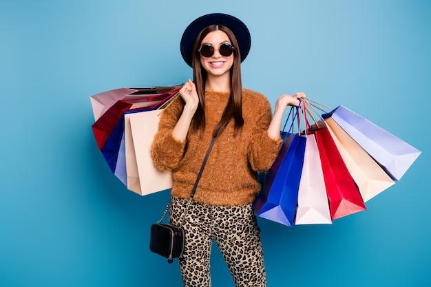 Retrato de uma garota alegre elegante estilo vintage, turista, caminhe inverno, feriado de primavera, loja boutique, segure muitas bolsas, use calças de suéter marrom clutch isoladas sobre parede de cor azul