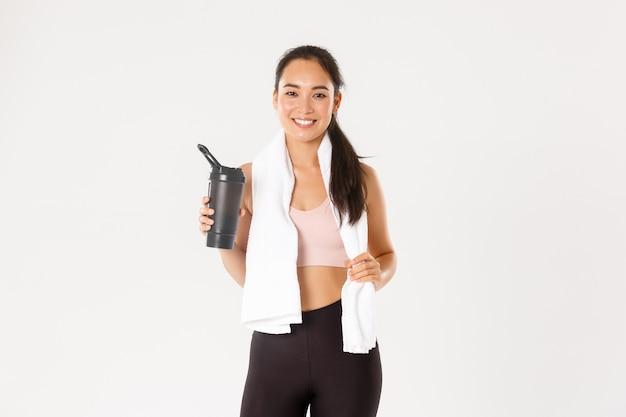 Retrato de uma garota asiática atraente fitness satisfeita com um sorriso fofo, parecendo satisfeito, enxugando o suor com uma toalha e água potável após o treino.